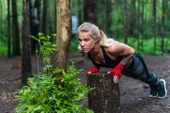 Muscular woman doing push-ups at park street work out stock images