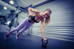 Muscular woman doing pushups with kettlebells Stock Photo
