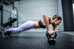Muscular woman doing pushups with kettlebells Royalty Free Stock Images