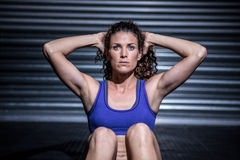 Muscular woman doing sit-ups. In crossfit gym Royalty Free Stock Photography
