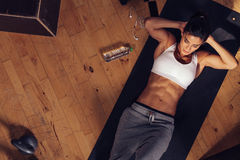 Muscular woman doing sit-ups in gym. Muscular woman doing sit-ups while lying on the floor. Overhead shot of female model doing stomach exercise in gym Stock Images