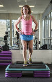 Muscular woman doing step aerobics Royalty Free Stock Photography