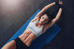 Muscular woman doing stretching workout on exercise mat Royalty Free Stock Photography
