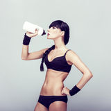 Muscular woman drinking water Royalty Free Stock Images