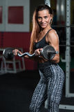 Muscular Woman Exercising Biceps With Barbell Stock Photo