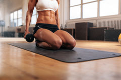 Muscular woman exercising with dumbbells Royalty Free Stock Image