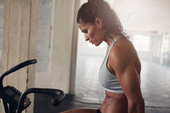 Muscular woman exercising on gym bike Royalty Free Stock Images