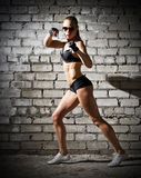 Muscular woman on grey brick wall (dark version) Stock Images