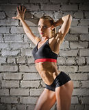 Muscular woman on grey brick wall (normal version) Stock Images