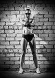 Muscular woman with gun on brick wall (monochrome version) Stock Image
