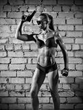 Muscular woman with gun on brick wall (monochrome version) Royalty Free Stock Images