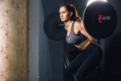 Muscular woman in a gym doing heavy weight exercises with barbell. Strong young woman exercising with barbell. Fit female athlete lifting heavy weights Stock Image