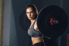Muscular woman in a gym doing heavy weight exercises with barbell. Muscular woman in a gym doing heavy weight exercises. Fitness female doing weight lifting at Stock Photo