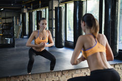 Muscular woman in a gym doing squats. Muscular woman in a gym doing heavy weight exercises. Young woman doing weight lifting at health club Royalty Free Stock Image