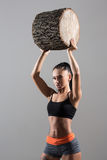 Muscular woman holding aloft a log Stock Image