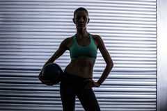 Muscular woman holding a medicine ball Royalty Free Stock Image