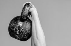 Muscular woman holding old and rusty kettle bell above her head. Royalty Free Stock Photos