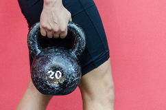 Muscular woman holding old and rusty kettle bell Stock Photo