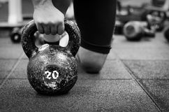 Muscular woman holding old and rusty kettle bell Stock Photos