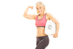 Muscular woman holding a weight scale Royalty Free Stock Photos