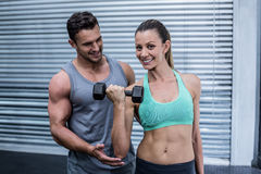 A muscular woman lifting dumbbells Stock Image