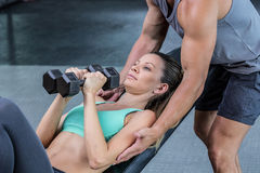 A muscular woman lifting dumbbells. Trainer assisting a muscular women lifting dumbbells Stock Image