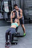 A muscular woman lifting dumbbells. Trainer assisting a muscular women lifting dumbbells Stock Images