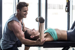 A muscular woman lifting dumbbells. Trainer assisting a muscular women lifting dumbbells Stock Photo