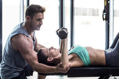 A muscular woman lifting dumbbells. Trainer assisting a muscular women lifting dumbbells Royalty Free Stock Images