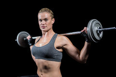 Muscular woman lifting heavy barbell Stock Photos