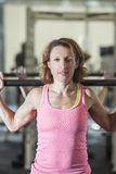 Muscular woman lifting weights Stock Photography