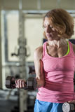 Muscular woman lifting weights Royalty Free Stock Images