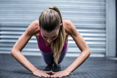 A muscular woman on a plank position Stock Photos