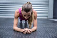 A muscular woman on a plank position Royalty Free Stock Photo
