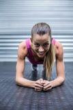 A muscular woman on a plank position Stock Photos