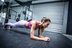 A muscular woman on a plank position Royalty Free Stock Photos