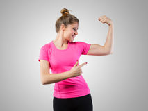 Muscular woman pointing on her bicep Stock Photography