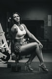 Muscular woman. Posing in the gym with dumbbell. Black and white Royalty Free Stock Photo