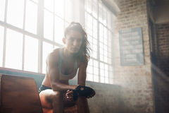 Muscular woman relaxing after workout at gym Royalty Free Stock Photo