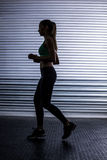 Muscular woman running in exercise room Stock Image