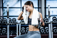 Muscular woman sitting on bench while holding bottle of water and a towel stock photography