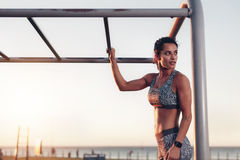 Muscular woman standing by monkey bars Stock Images