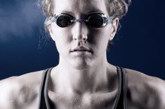 Muscular woman swimmer. Portrait of a looking at camera strong muscular woman swimmer, blue toned on blue background Stock Image