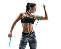 Muscular woman with tape measures the size of his biceps royalty free stock images