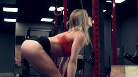 Muscular woman working out in the gym lifting weights stock footage