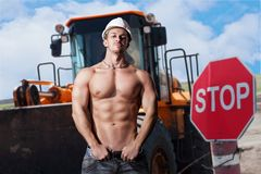 Muscular work on the background dump trucks Royalty Free Stock Photography
