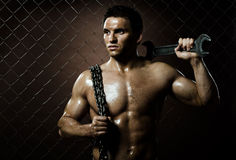 Muscular worker. The beauty muscular worker  man,  with big wrench and  chain in hands, on netting fence background Royalty Free Stock Image