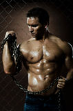 Muscular worker. The beauty muscular worker  man,  with big  chain in hands, on netting fence background Stock Image