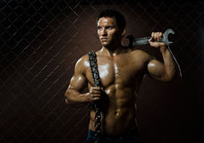Muscular worker. The beauty muscular worker  man,  with big wrench and  chain in hands, on netting fence background Stock Photo