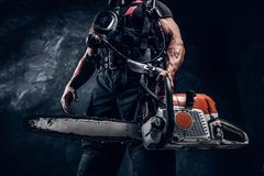 Portrait of muscular man with chainsaw and respirator royalty free stock images